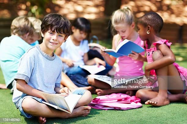 Souriant garçon avec des amis à étudier en arrière-plan