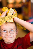Smiling boy with handful of tickets on his head