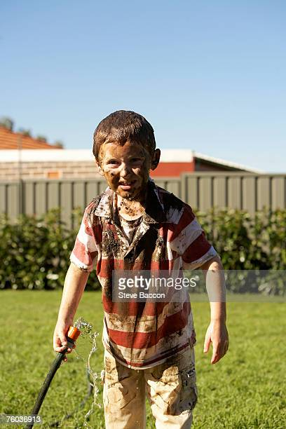 Smiling boy (6-7) with mud on face and t-shirt holding water hose, portrait
