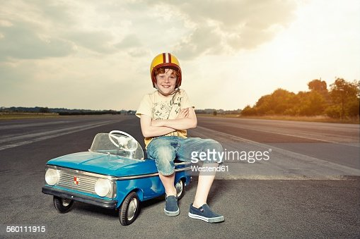 Smiling boy with pedal car on race track