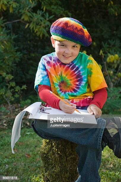 Smiling boy writing outdoors
