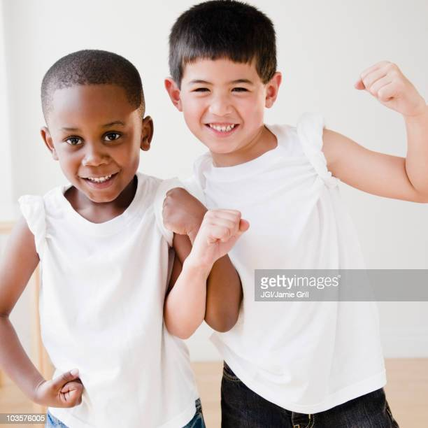 Smiling boys flexing biceps