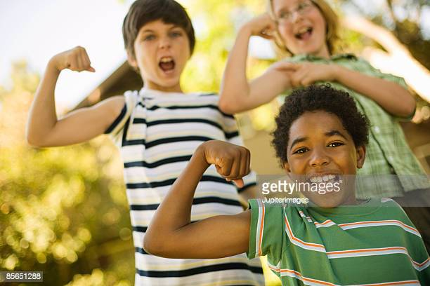 Smiling boys flexing muscles