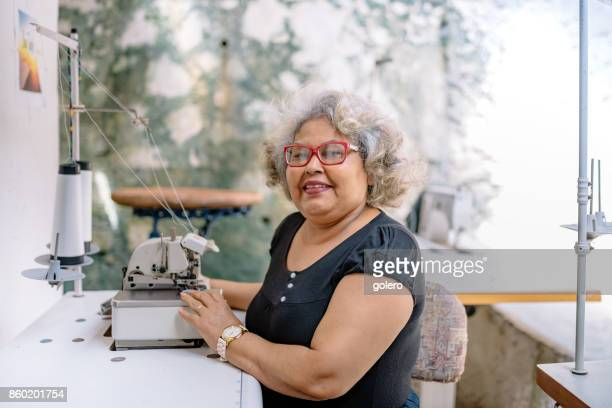 smiling brazilian senior woman at sewing machine in tailor work room