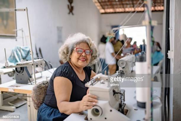 lächelnde senior Brasilianerin an Nähmaschine im Arbeitsraum Schneider