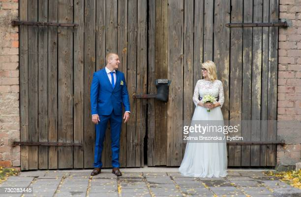 Smiling Bridal Couple Looking At Each Other While Standing Against Door Of Barn