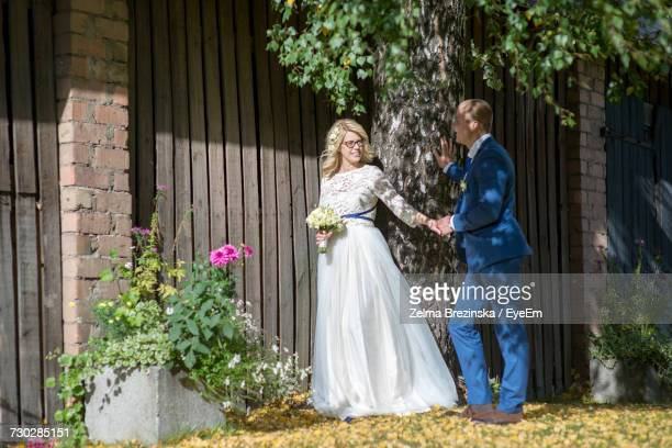Smiling Bridal Couple Looking At Each Other While Standing By Barn
