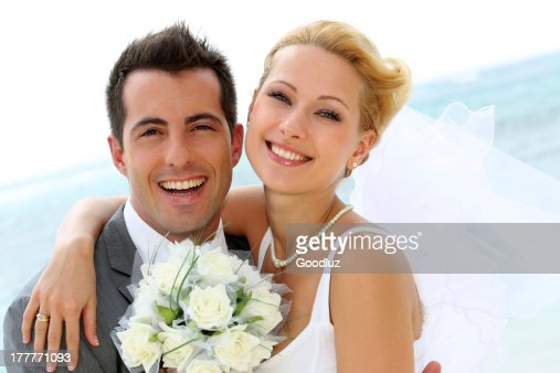 Smiling bridal couple with bouquet of flowers : Stock Photo