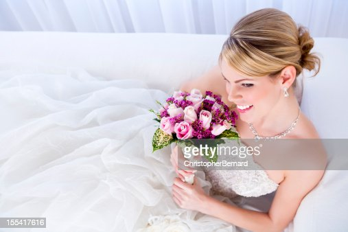 Smiling bride holding pink bouquet