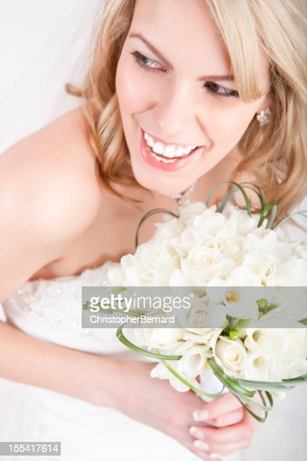 Smiling bride holding white bouquet