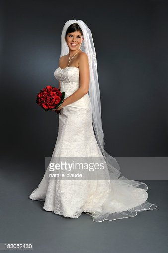 Smiling bride in wedding gown holding bouquet of roses
