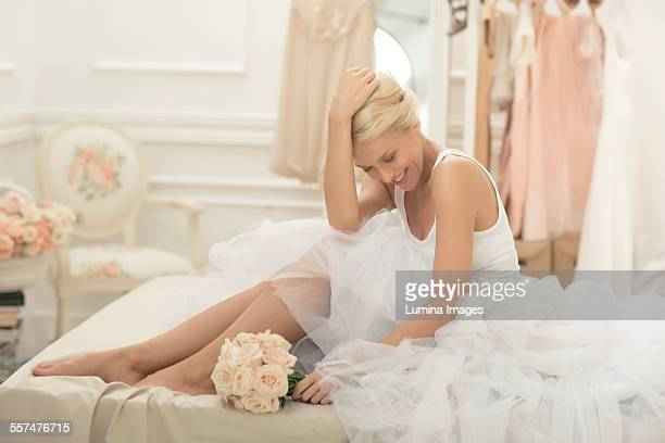 Smiling bride sitting with bouquet on bed