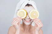 Smiling brunette woman holding two slice of lemon in front of her face. woman with moisturizing facial mask. Beauty and skin care concept