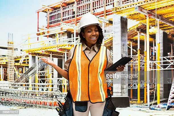 Smiling building contractor presenting outdoors