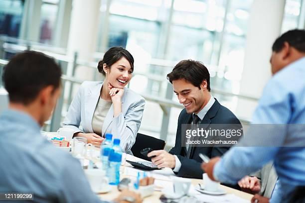 Lächelnd Geschäftsmann sitzt für ein Vorstandstreffen
