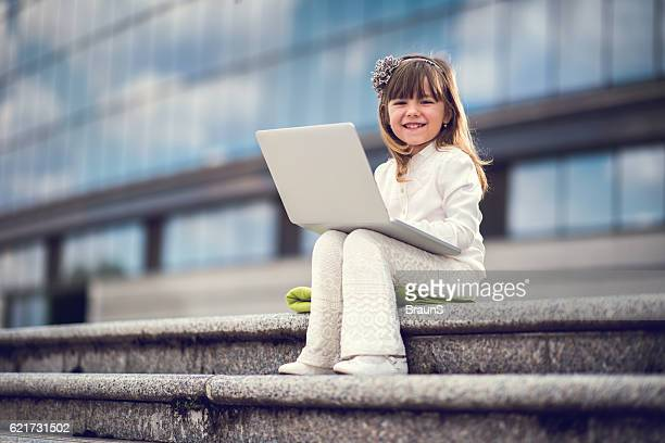 Smiling business girl using computer on staircase.