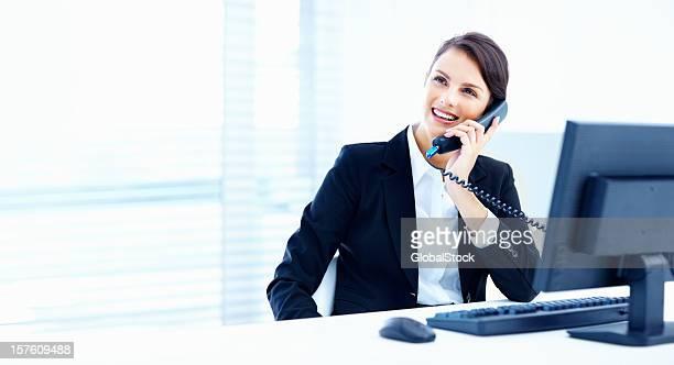 笑顔のビジネス女性のオフィスで電話で話している