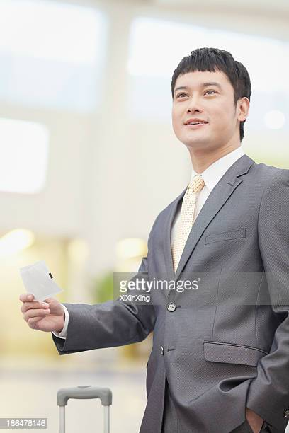 Smiling business man holding flight ticket