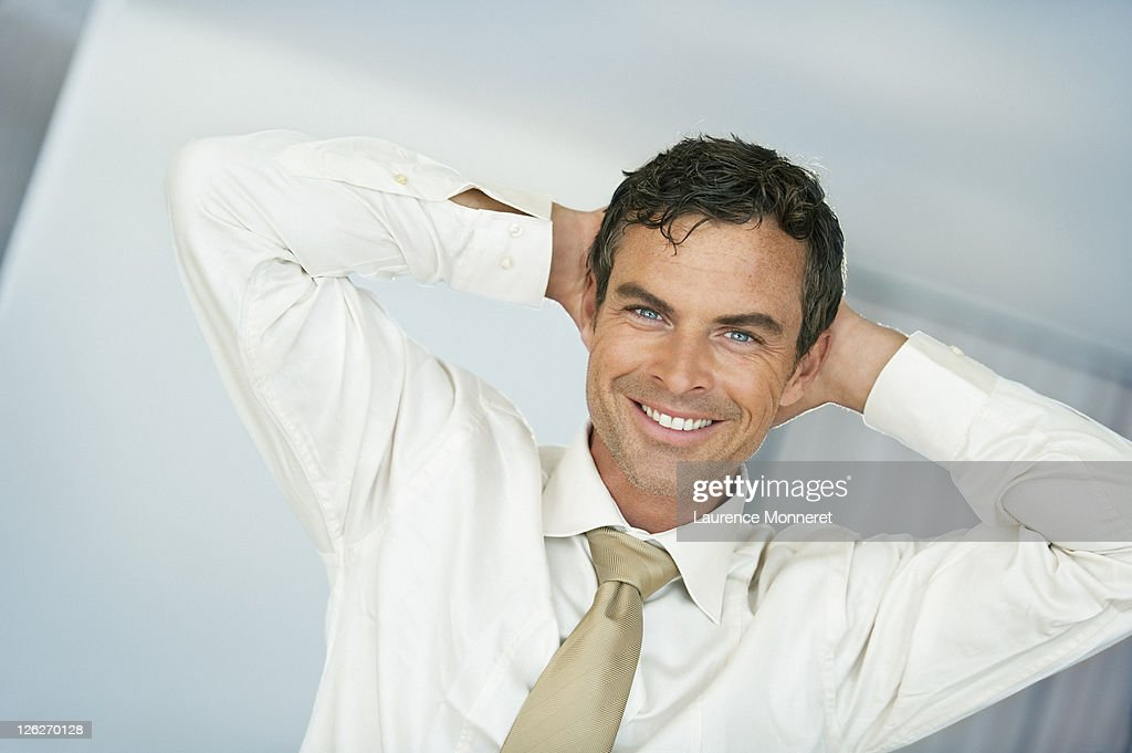 Smiling business man relaxing hands behind head