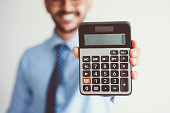 Closeup of blurred smiling young business man holding calculator and showing zero on it. Free of charge concept. Isolated front view on grey background.