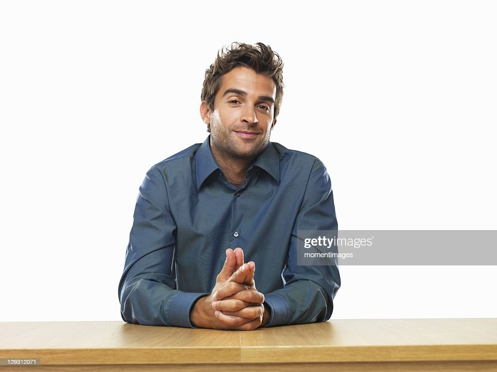 Smiling business man sitting at table with hands clasped : Stock Photo