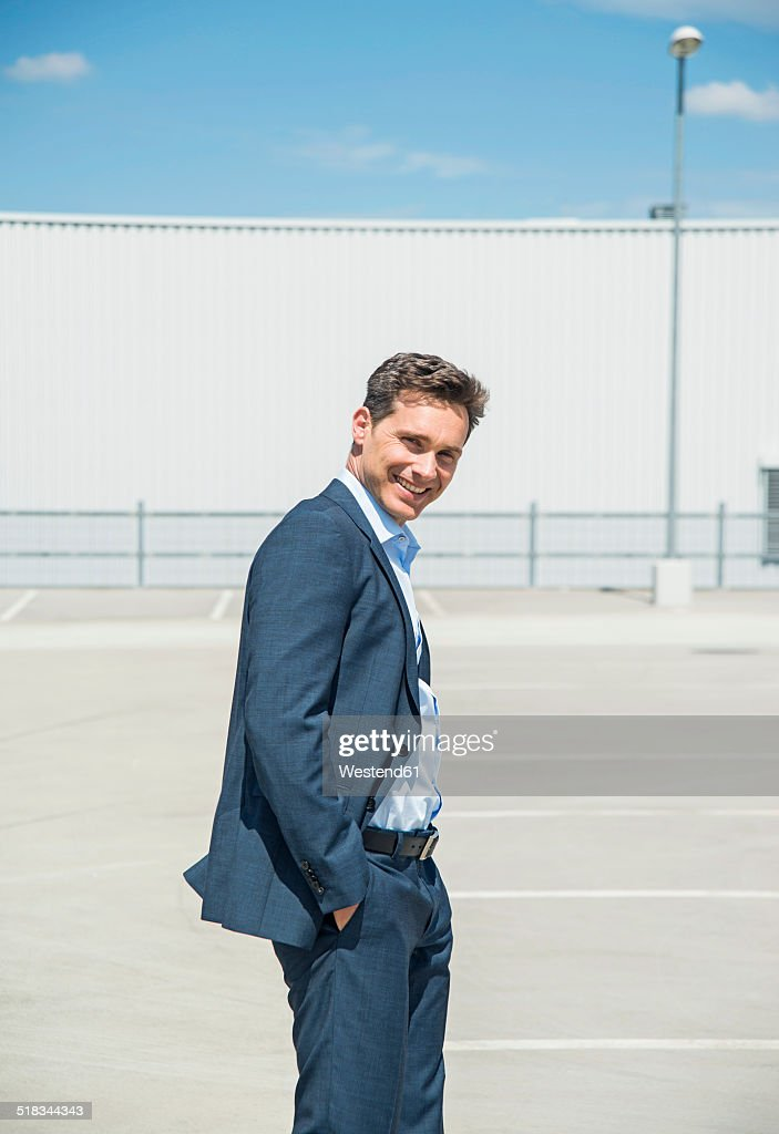 Smiling business man standing on parking level