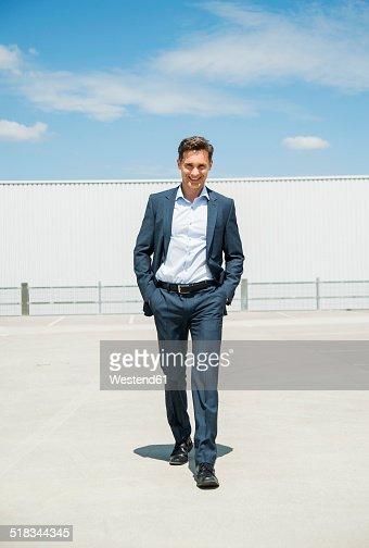 Smiling business man walking on parking level