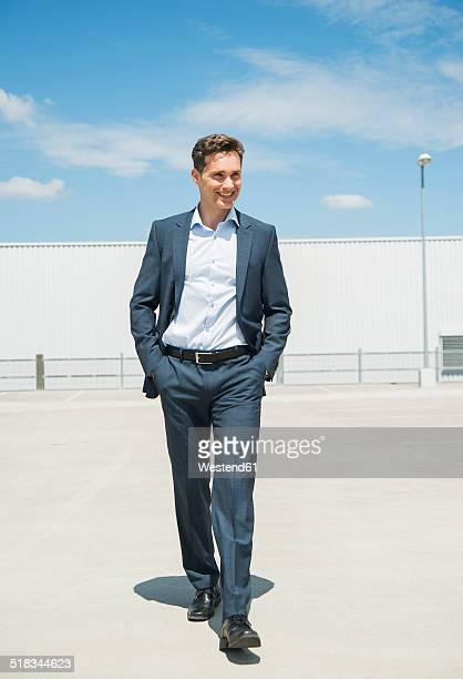 Smiling business man walking on parking level