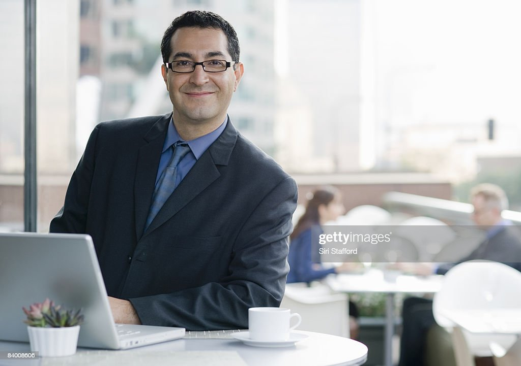 Smiling business man with computer in cafe. : Stock Photo