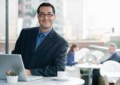 Sorridente Homem de negócios com computador no café.