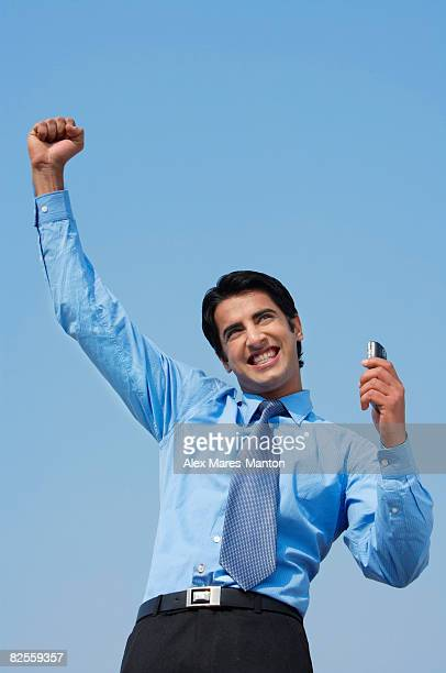 smiling business man with fist in air, phone in hand