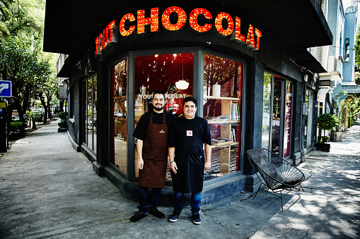 Smiling business owners in front of chocolate shop