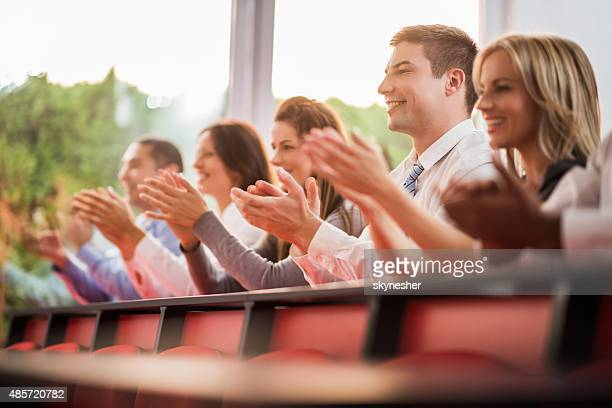 Smiling business people applauding on a conference.