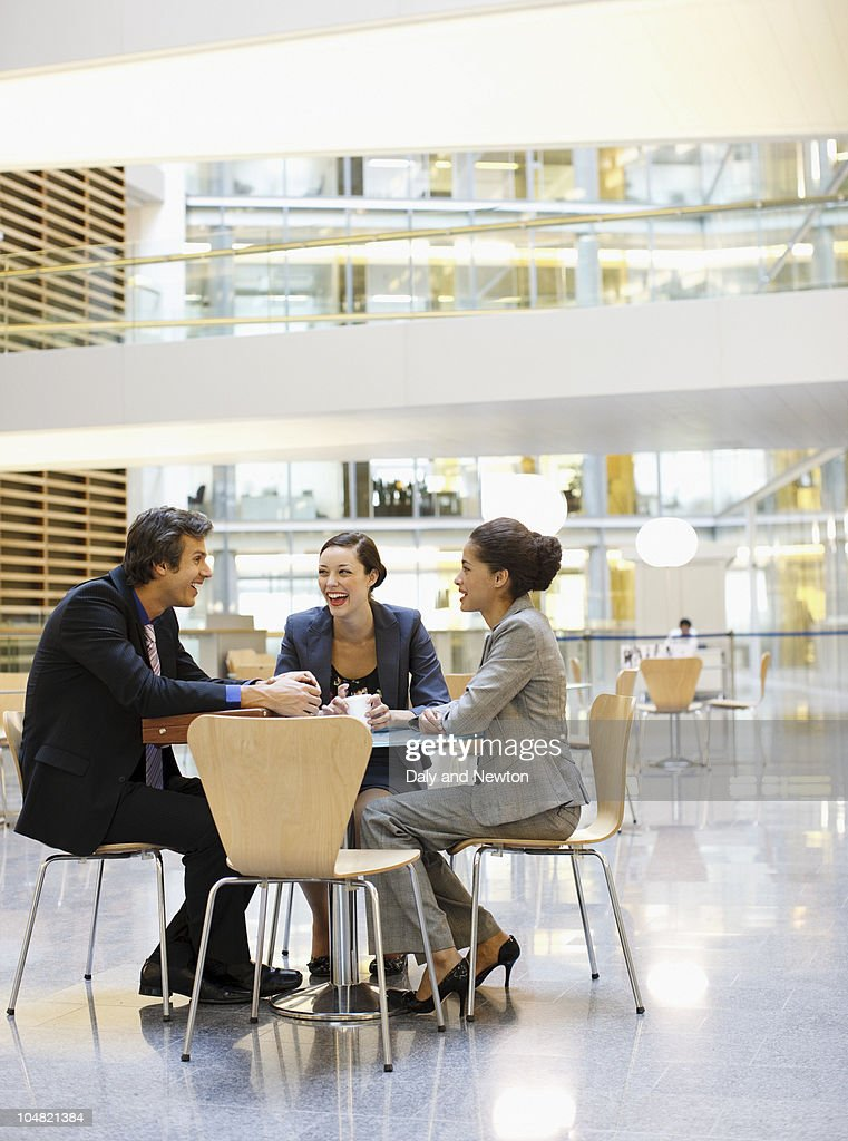 Smiling business people having a meeting at cafeteria table