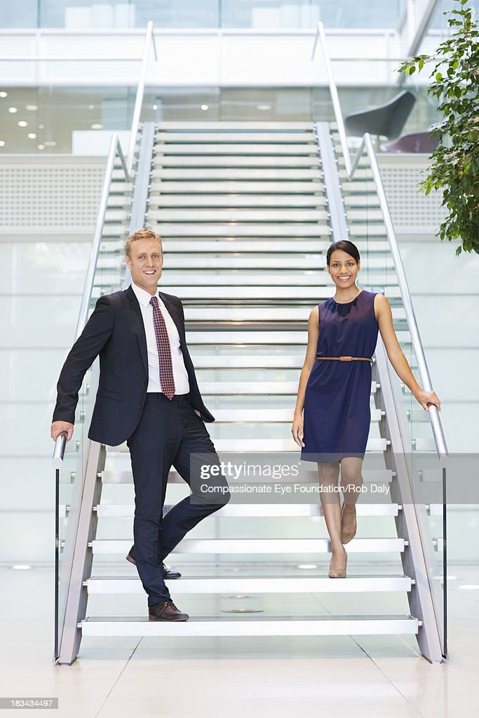 Smiling business people in lobby : Stock Photo