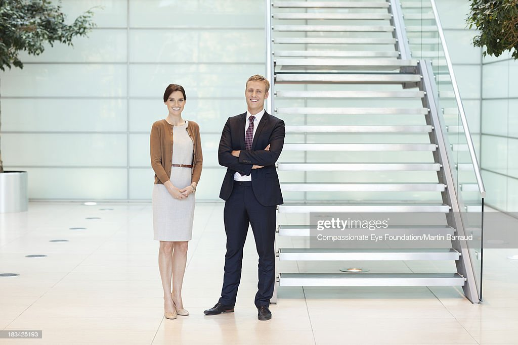 Smiling business people in modern lobby : Stock Photo