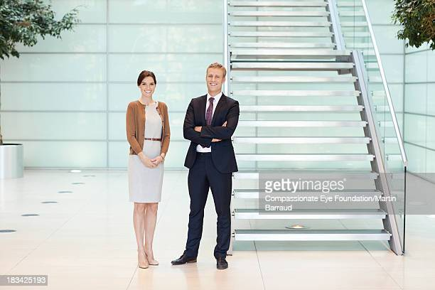 Smiling business people in modern lobby