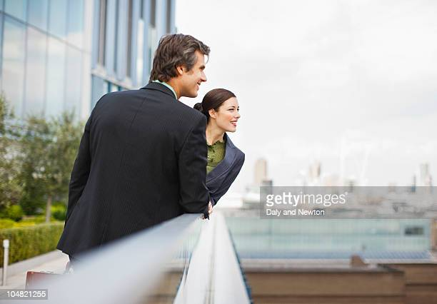 Smiling business people leaning on railing outside office building