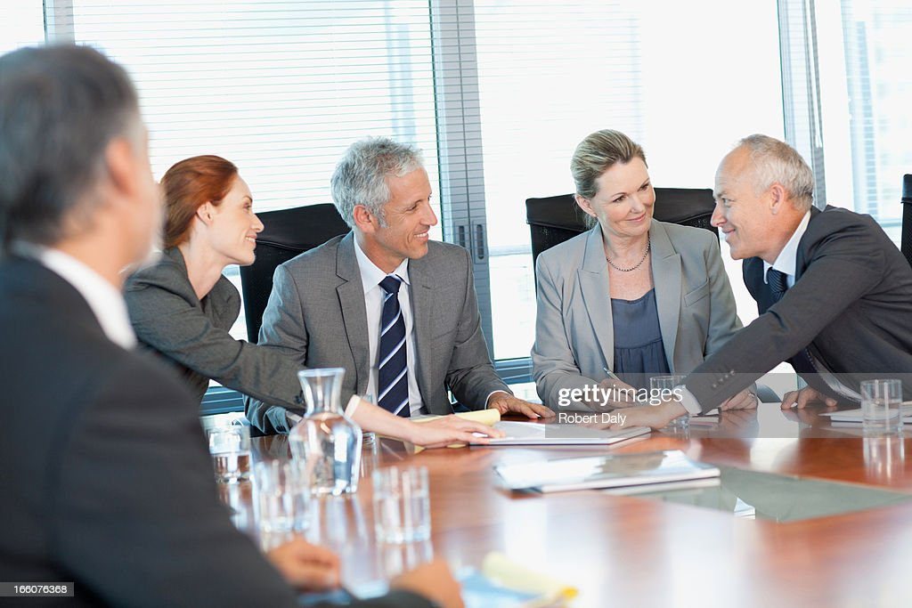 Smiling business people meeting at table in conference room : Stock Photo