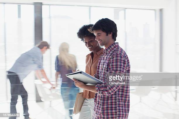 Smiling business people reviewing paperwork in office