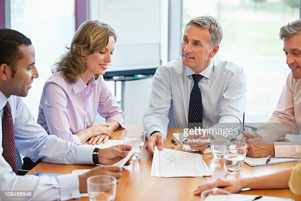 Smiling business people sitting at conference table in a meeting at board room