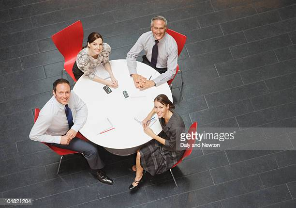 Smiling business people sitting at round table and having a meeting