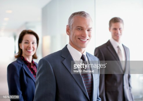 Smiling business people standing in office : Stock Photo