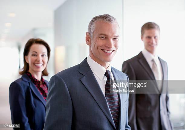 Lächelnde Geschäftsleute stehen im Büro