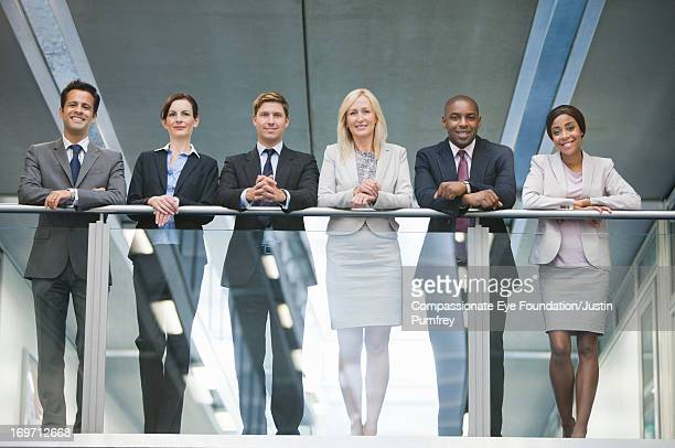 Smiling business people standing on atrium balcony