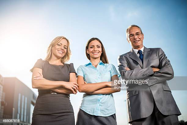 Smiling business people with arms crossed looking at camera.