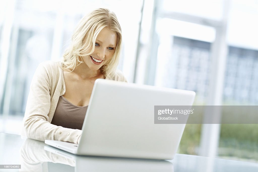 Smiling business woman busy with her laptop : Stock Photo
