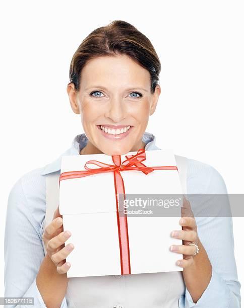 Femme d'affaires souriante, ce qui vous offre une boîte cadeau sur fond blanc