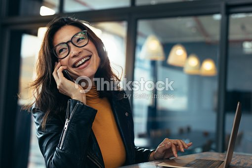 Smiling business woman in casuals talking on phone : Stock Photo