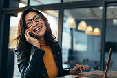 Cheerful asian female talking on mobile phone while sitting on desk with laptop. Business woman in casuals making a phone call and laughing.